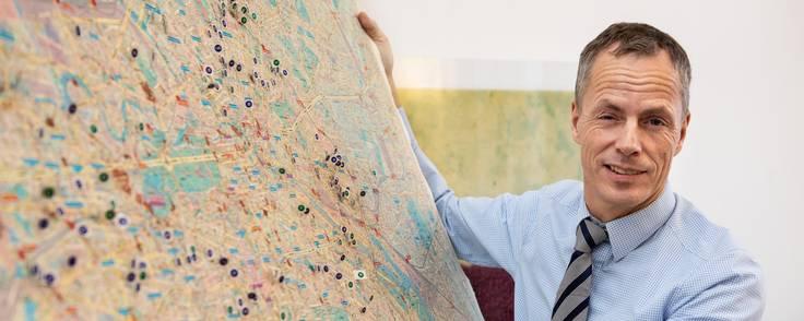 I en årrække har Hans-Oluf Meyer, der på billedet holder et bykort over Berlin, stået bag storbyens eneste selvstændige danske advokatkontor. Foto: Christian Jørgensen
